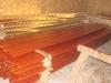 Die zahlreichen schmalen Latten für die abschließende Fassadengestaltung werden von Hand mit rotbrauner Lasur behandelt.